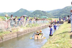 手作りの段ボール製の舟で綾部用水を下る綾部青年会議所主催のイベント「綾部D―1グランプリ~さあ、やろうぜ! ダンボ!~」が28日、川糸町の第1市民グラウンドとその西側を流れる綾部用水で開かれ、市内の子ども23組46人とその保護者らが参加した。