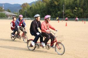 2人以上の座席とペダルを装備した「タンデム自転車」に乗れる府北部で初めての体験会が17日、上杉町の市総合運動公園グラウンドで開かれた。後部座席には視覚障害者も乗れるのが魅力の一つで、市内外から参加した視覚障害者ら8人が、支援者など約25人と一緒に、久々の自転車の爽快感を味わいながら交流を楽しんだ。