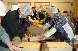 老富町の老富会館で19日、「あやべ特別市民制度」の登録者に送る「ふるさと産品」の梱包・発送作業が行われ、作業を受託した水源の里・老富(西田昌一代表)のメンバー14人らが約2千箱の箱詰め作業に励んだ。