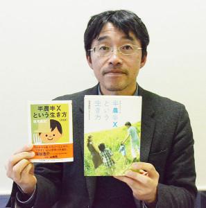 「半農半Xという生き方」の文庫版(左)と、最初に出版したハードカバー版を持つ塩見さん