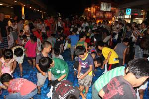 西町1丁目の西町アイタウン1番街で9日夜、往年の「土曜夜の市」を継承する「日曜夜の市」(日曜夜の市実行委員会主催)が開かれた。メーンイベントの魚つかみ大会には100人以上の子どもたちが参加。市街地の夜が、特設プールを泳ぐアユやウナギなどを夢中で追いかける子どもの歓声に包まれた。
