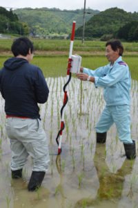 田んぼで田の中に刺した棒にヘビが巻き付いているような光景が篠田町で見られる。実はこれ、水田センサーシステム。多くの水田を持つ大規模農業者にとって水管理は大変な作業だが、田んぼへ水量や水温などを調べに行かなくてもスマートフォン(スマホ)やタブレット端末を使って情報が得られるというもの。