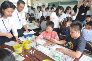 綾部中学校と綾部・中筋・吉美3小学校は今年度、「アート紡(つむぎ)プロジェクト」と名付けた事業を共同で取り組む。これは、3小学校の6年生たちが作った和紙製のランプシェード約200個を来年1月末、宮代町の綾部中学校の第2体育館内に並べて文字を作るというもの。2日には綾部中に集まった3小学校の児童会役員らに対し、中学生たちが今回のプロジェクトについて説明し、成功に向けて協力し合うことを確認した。