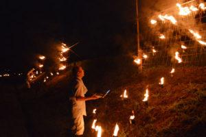 17日夜、向田町の田んぼの法面(のりめん)に「元気な里に… 奉灯 向田かんのん」の火文字が浮かび上がった。