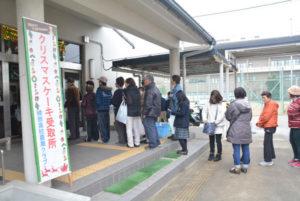 川糸町の綾部高校由良川キャンパス(東分校)で21日、市民らの行列ができた=写真。この行列はクリスマスケーキの購入を予約し、受け取りに来た人たち。