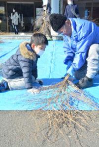 鷹栖町の市基幹集落センターで4日、地元の小学生らが西村勝さん(86)=西原町=の指導で竹ぼうきの作り方を学んだ。