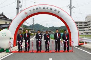 市が平成23年度から6年がかりで幅員拡幅などに取り組んできた市道青野豊里線の改良工事が完了し15日、青野町の同市道に特別に設けられた式典場で開通式が行われた。