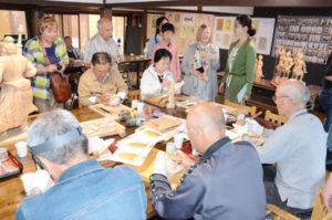 カナダからの旅行者の一行らが20日、梅迫町で仏像彫刻を楽しんでいる「空の会」(四方和行代表)のアトリエを訪問