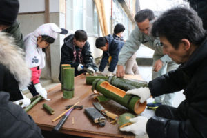 市シルバー人材センターが観光の体験プログラムの一環として昨年に引き続いて企画した「ミニ門松つくり体験」が22日、十倉名畑町の黒谷和紙工芸の里で開かれ、福知山市や舞鶴市、福井県おおい町など市外在住者も含む15組20人が、竹を切るところから始める本格的な門松づくりを楽しんだ。