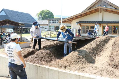 鍛治屋町の市里山交流研修センターで今月から、「ゼロ農」と名付けた新プロジェクトが始まった。これは敷地内の一角にある赤土の広場(約100平方㍍)を「ゼロ」の状態から畑に整備し、交流の場にしていくというもの。同センターの指定管理団体であるNPO法人里山ねっと・あやべの呼び掛けに応じた府立農業大学校や京都産業大学、オムロン綾部事業所、あやべボランティア総合センターなどの協力を得て、22日から作業が始まった。
