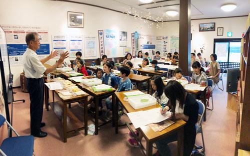 グンゼ(廣地厚社長)は20日、青野町にあるグンゼ博物苑で夏休みの子ども向けイベント「蚕都・綾部の今昔探訪」と題して養蚕体験を開催し、親子10組27人が参加して蚕の飼育方法などを学んだ。