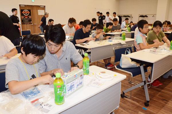 小学生に「ものづくり」や「科学技術」について興味を持ってもらおう―と、綾部鉄工工業協同組合(大槻浩平理事長、28社)は「あやべロボットコンテスト2019」(市・京都工芸繊維大学共催)を初開催。市内5小学校から4~6年生21人が申し込み、1日目として21日には青野町の市ものづくり交流館で親子らがロボット製作に取り組んだ。