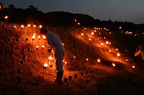向田町で17日夜、長福寺で行われる「向田観音祭」の協賛行事である火文字奉灯が今年もあり、新元号にちなんで「祝 令和元年 奉灯 向田かんのん」の火文字が田んぼの法面に灯された。