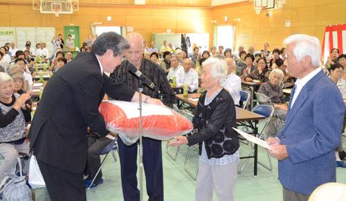 昨年から中上林と奥上林の両地区が合同で開いている「上林地区敬老会」(奥と中の両地域振興協議会主催)が15日、140人の高齢者が出席して八津合町の上林小中一貫校体育館で催された。