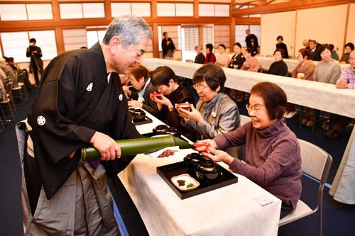 大本本部の「七草粥(がゆ)接待」が9日、上野町の大本長生殿(白梅殿)で行われ、訪れた市民らは春の七草が入ったお粥を味わいながら今年一年の無病息災を願った。
