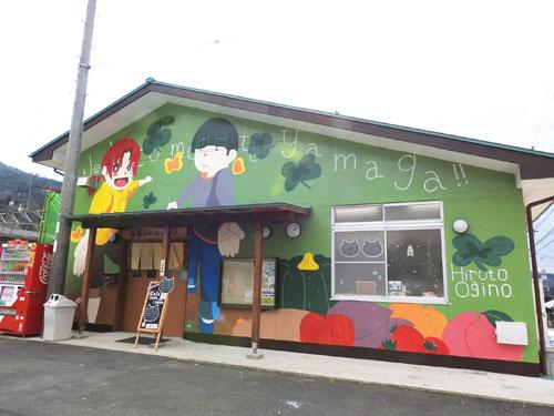 建物の外壁を大きなキャンバスにした「ウオールペイント(壁面塗り)」がJR山家駅前(上原町)にこのほど完成した。「やまが元気プロジェクト委員会」(谷口和紀委員長)の同駅運営委員会が山家駅前にある「山家ふれあいの駅」で取り組んでいたもので、男女二人のオリジナルキャラクターが山家への来訪を歓迎している。