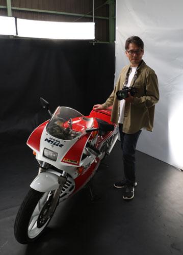 「ノブ撮り」の名で全国のバイクファンを魅了するバイク専門の写真家が綾部にいる。上延町の田中伸明さん(44)だ。本格的なスタジオセットを駆使したバイク撮影サービスを全国で初めて事業化した先駆者であり、創業5年で撮影したバイクは5千台超。また同時に、写真が好きな全国のライダー17人で活動する写真家団体「MPG」の一員でもあり、9、10月には東京、大阪での巡回展が決まるなど、その活動が注目されている。