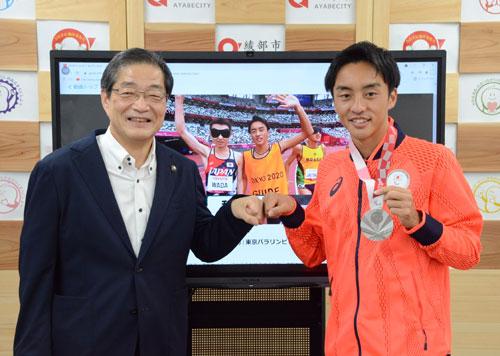 東京2020パラリンピック競技大会・陸上競技の男子1500㍍(視覚障害T11)で銀メダル、男子5千㍍(同)で銅メダルを獲得した和田伸也選手(44)の伴走者(ガイドランナー)を務めた綾部出身の長谷部匠選手(24)が9日、市役所に山崎善也市長を表敬訪問し、多くの市職員らから熱烈な歓迎を受けた。